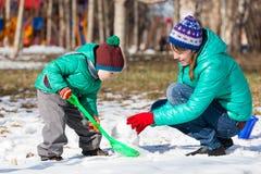 Pupazzo di neve della costruzione del figlio e della madre nell'inverno Immagini Stock Libere da Diritti