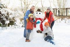 Pupazzo di neve della costruzione della famiglia in giardino Fotografie Stock Libere da Diritti