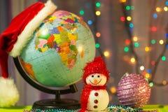 Pupazzo di neve di Buon Natale sui precedenti del globo in un cappuccio di Santa Claus Immagine Stock