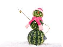 Pupazzo di neve di natale dell'anguria con la campana e decorazioni di Natale in cappello e sciarpa rosa Concetto di festa per i  Immagini Stock