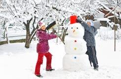 Pupazzo di neve e bambini Fotografia Stock