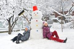 Pupazzo di neve e bambini Fotografia Stock Libera da Diritti