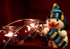 Pupazzo di neve e candele di fondo rosso scuro del tessuto Immagine Stock
