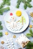 Pupazzo di neve di Natale fatto della gelatina di frutta e della caramella gommosa e molle su un piatto con i rami e le decorazio fotografia stock libera da diritti