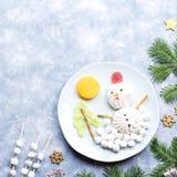 Pupazzo di neve di Natale fatto della gelatina di frutta e della caramella gommosa e molle su un piatto con i rami e le decorazio fotografie stock libere da diritti