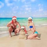 Pupazzo di neve sabbioso in cappello di Santa e giovani coppie felici alla spiaggia Fotografie Stock