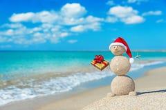Pupazzo di neve sabbioso sorridente alla spiaggia in cappello di natale con il regalo dorato Fotografia Stock
