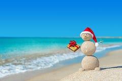 Pupazzo di neve sabbioso sorridente alla spiaggia in cappello di natale con il regalo dorato Immagine Stock Libera da Diritti