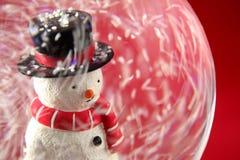 Pupazzo di neve in Snowglobe con priorità bassa rossa fotografie stock libere da diritti