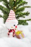 Pupazzo di neve sorridente con l'albero di Natale del contenitore e di regalo Fotografia Stock Libera da Diritti