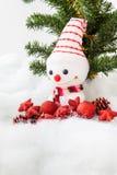 Pupazzo di neve sorridente con la decorazione di natale e l'albero di Natale Fotografia Stock