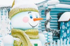 Pupazzo di neve sui precedenti di una casa di inverno Fotografia Stock Libera da Diritti