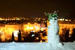 Pupazzo di neve sveglio su un fondo di una città di notte fotografie stock