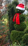 Pupazzo di neve verde che porta uno spiritello malevolo e una sciarpa immagini stock