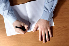 Pupil boy at a desk writing in a exercise book. Top view Royalty Free Stock Images