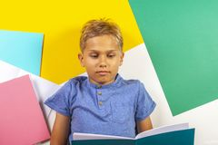 Pupil boy reading book notebook doing homework. Top view, colorful background Royalty Free Stock Image