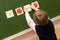 The pupil with cards at a blackboard. Boy at the lesson in the classroom Stock Image