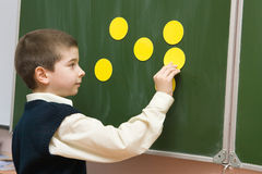 The pupil with cards at a blackboard. Boy at the lesson in the classroom Stock Photography