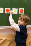 The pupil with cards at a blackboard. Boy at the lesson in the classroom Royalty Free Stock Photos