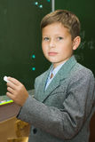The pupil with a chalk at a school board. The boy in a classroom at a lesson costs about a board with a chalk in a hand Stock Photos