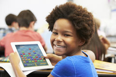 Pupil In Class Playing a Game on a Tablet Royalty Free Stock Photography