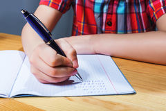 Pupil at the desk writing in notebook closeup view Stock Photos