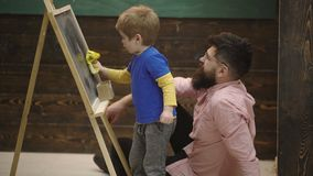 Pupil drawing on chalkboard. Teacher controls learning process. Father teaching son. Pupil with teacher at school. Side. Pupil drawing on chalkboard. Teacher stock video footage
