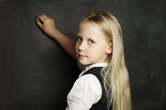 Pupil draws with chalk on blackboard Royalty Free Stock Photos