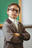 Pupil dressed up as teacher with arms crossed. Portrait of pupil dressed up as teacher with arms crossed in a classroom Royalty Free Stock Photography