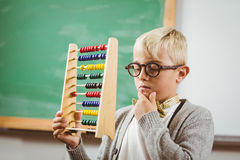 Pupil dressed up as teacher holding abacus. In a classroom Royalty Free Stock Images