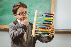 Pupil dressed up as teacher holding abacus. In a classroom Stock Photos