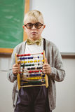 Pupil dressed up as teacher holding abacus. Portrait of pupil dressed up as teacher holding abacus in a classroom Stock Image