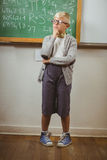 Pupil dressed up as teacher thinking in front of chalkboard. In a classroom Stock Photography