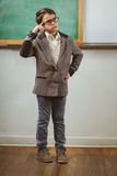 Pupil dressed up as teacher thinking in front of chalkboard Stock Images