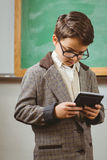 Pupil dressed up as teacher using calculator. In a classroom Royalty Free Stock Image