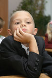 Pupil of an elementary school. At a lesson behind a school desk Stock Images