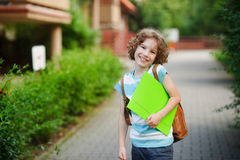 Pupil of elementary school. The boy of 8-9 years stands on the sidewalk and with a cheerful smile looks in the camera. It has fair curly hair and blue eyes. In Royalty Free Stock Photography