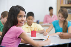 Pupil in elementary school classroom. Female pupil in elementary school classroom Stock Photo