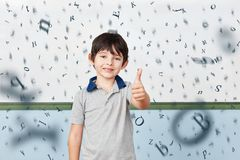 Pupil in elementary school keeps thumbs up stock images