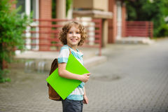 Pupil of elementary school stand in a half-turn to the camera and joyfully smiles Royalty Free Stock Image