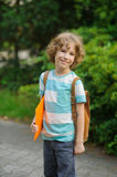 The pupil of elementary school stand on a schoolyard and smiles. Royalty Free Stock Photography