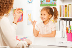 Pupil exercises putting fingers as her teacher. Clever pupil exercises putting fingers as her teacher at the desk with geometric figures Royalty Free Stock Photo
