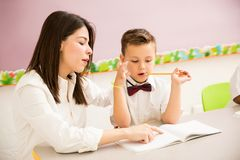 Pupil getting some help from his teacher. Male preschool student wearing uniform and getting some help from his teacher in a classroom stock images