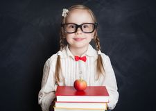 Pupil girl in classroom on blue chalkboard background,. Education concept royalty free stock photo