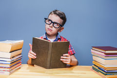 Pupil in glasses getting knowledge from a textbook Stock Photos