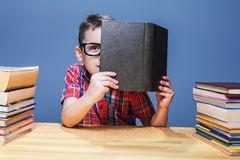 Pupil in glasses getting knowledge from a textbook Royalty Free Stock Photography