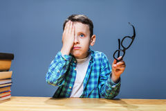 Pupil with glasses in hands checks vision Royalty Free Stock Images