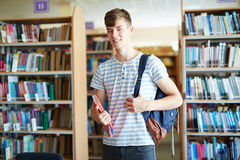 Pupil. Guy with satchel looking at camera in library or classroom Royalty Free Stock Photos