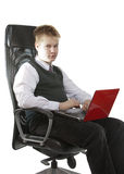 Pupil of high classes in a school uniform with a notebook sits in a working seat Royalty Free Stock Photography