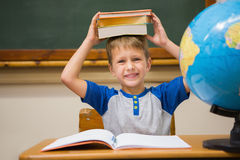 Pupil holding books on his head Royalty Free Stock Photo